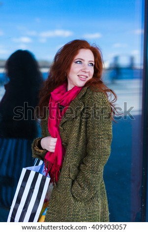 Portrait of a beautiful redhead woman in the shopping mall, smile, looking up dreaming - stock photo
