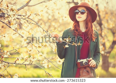 Portrait of a beautiful redhead women in cloak and hat with camera in blossom apple tree garden in spring time on sunset. - stock photo