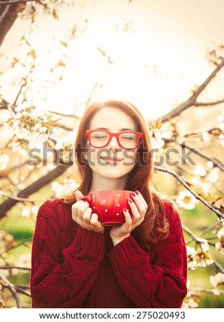 Portrait of a beautiful redhead women in red sweater with cup in blossom apple tree garden in spring time on sunset. - stock photo