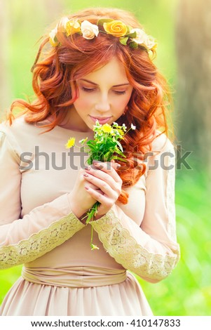 Portrait of a beautiful romantic girl enjoying aroma of a gentle wild flowers in the spring park, sensual fashion look of the forests nymph - stock photo