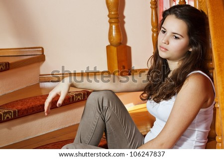 Portrait of a beautiful sad teenage girl sitting at home - stock photo