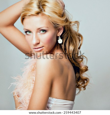 Portrait of a beautiful sensual and sexy blonde girl in pink feather Boas in Studio, close-up - stock photo