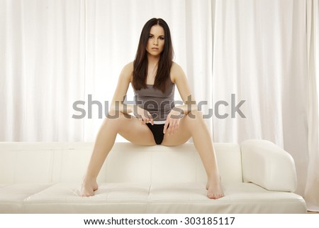 Portrait of a beautiful sensuality and attractive young adult pretty brunette woman posing in grey shirt on the white couch - stock photo