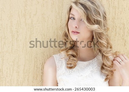 Portrait of a beautiful sexy smiling happy girl with big full lips with blond hair in a white dress on a sunny bright day - stock photo