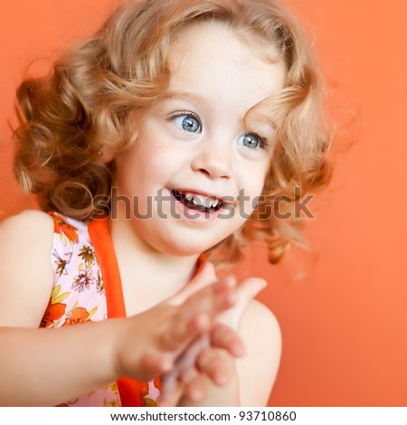 Portrait of a beautiful small girl with gorgeous blue eyes and blonde curly hair clapping her hands on an orange background - stock photo