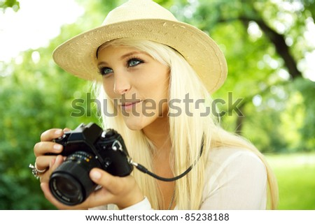 Portrait of a beautiful smiling female with a camera. - stock photo