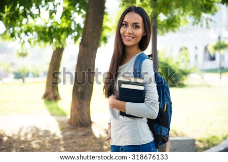 Portrait of a beautiful smiling student standing outdoors with books - stock photo