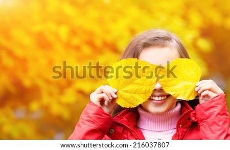 portrait of a beautiful smiling teenage girl with yellow leaves in autumn - stock photo