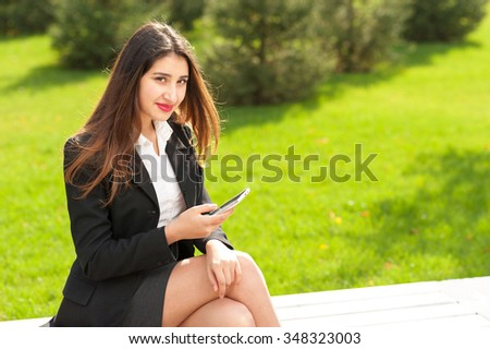 Portrait of a beautiful smiling young business woman sitting on a bench outdoor with cell phone (mobile). Bright green grass as background. - stock photo