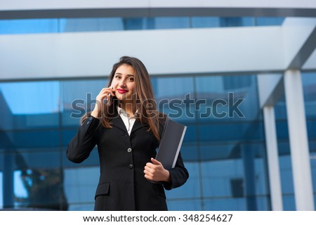 Portrait of a beautiful smiling young business woman speaking by the cell phone (mobile). Modern building as background. - stock photo