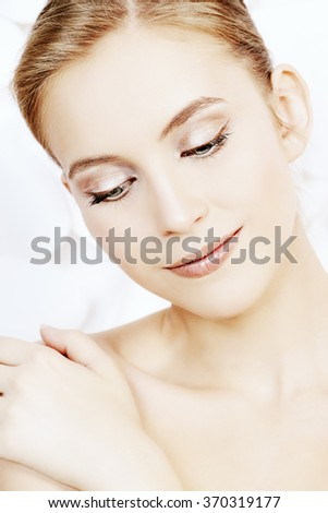 Portrait of a beautiful smiling young woman with natural make-up over background. Spa girl. Skincare, healthcare. Studio shot.  - stock photo
