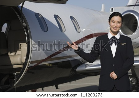 Portrait of a beautiful stewardess gesturing by airplane at airfield - stock photo