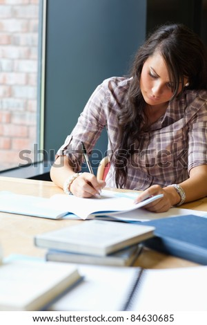 Portrait of a beautiful student writing an essay in a library - stock photo