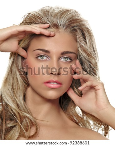 portrait of a beautiful tanned young woman with long blond curly hair wearing natural make-up touching her face on white background - stock photo