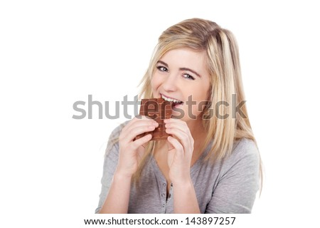 Portrait of a beautiful teenage girl eating chocolate against white background - stock photo