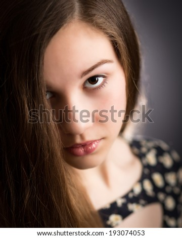 Portrait of a beautiful teenage girl with brown eyes and red glossy lips looking up in the camera - stock photo