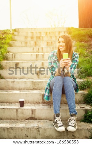 Portrait of a beautiful teenage student girl sitting on stairs in park with smart phone and coffee cup. Sunny summer day. Modern and casual lifestyle. - stock photo