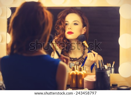 Portrait of a beautiful woman as applying makeup near a mirror. Photo in retro color style. - stock photo