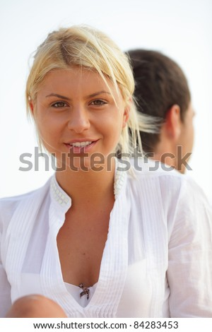 Portrait of a beautiful woman at the beach with her boyfriend at her back - stock photo