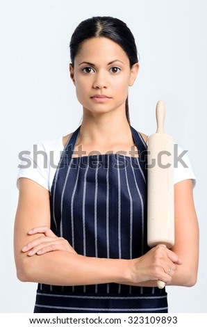 Portrait of a beautiful woman baker with a serious expression, full of focus and determination, holding a rolling pin  - stock photo