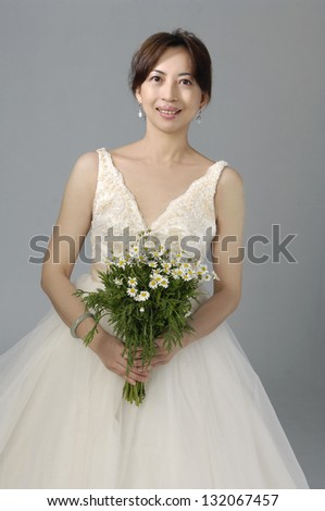 Portrait of a beautiful woman dressed as a bride with bouquet of flowers - stock photo