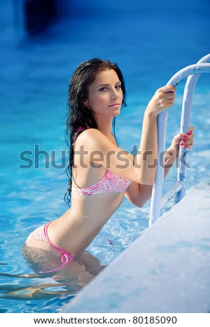 Portrait of a beautiful woman getting out of a swimming pool - stock photo