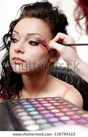 Portrait of a beautiful woman having makeup applied by makeup artist - stock photo
