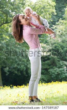 Portrait of a beautiful woman holding baby in park - stock photo