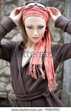 portrait of a beautiful woman in a sling on the street, against a stone wall - stock photo