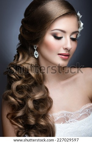 Portrait of a beautiful woman in a wedding dress in the image of the bride. Picture taken in the studio on a grey background - stock photo