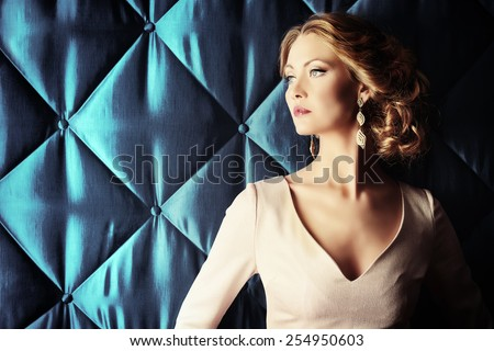 Portrait of a beautiful woman in elegant evening dress posing over vintage background. Jewellery.  Fashion shot. Hairstyle. - stock photo