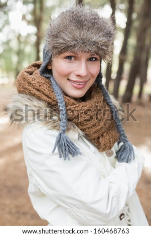 Portrait of a beautiful woman in fur hat with woolen scarf and jacket in the woods - stock photo