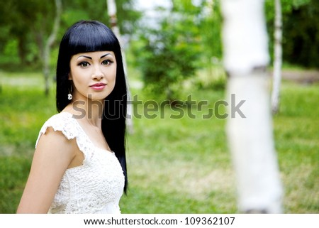 Portrait of a beautiful woman in summer garden - stock photo