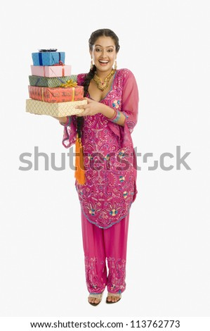 Portrait of a beautiful woman in traditional dress holding gifts and smiling - stock photo