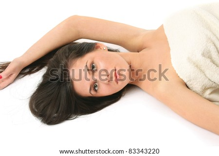Portrait of a beautiful woman lying on the floor with a towel isolated on white background. - stock photo