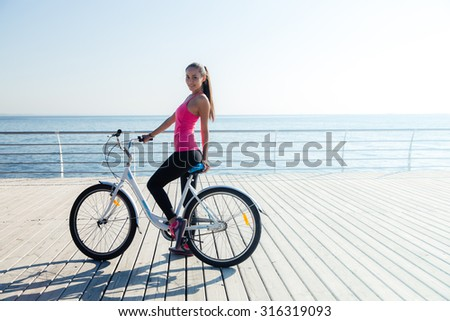Portrait of a beautiful woman on bicycle outdoors - stock photo