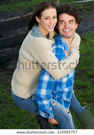 Portrait of a beautiful woman piggyback handsome man outdoors - stock photo