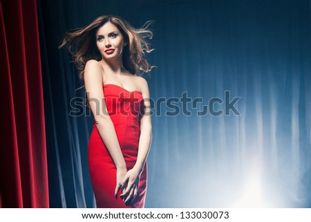Portrait of a beautiful woman posing in a red dress in front of the scenes - stock photo
