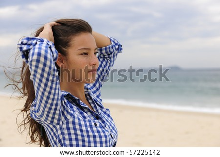 portrait of a beautiful woman relaxing by the sea with copy space - stock photo