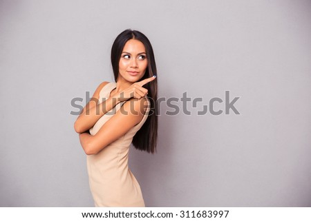 Portrait of a beautiful woman showing finger away over gray background - stock photo