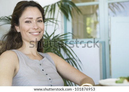 Portrait of a beautiful woman sitting at home with plants and smiling at camera. - stock photo