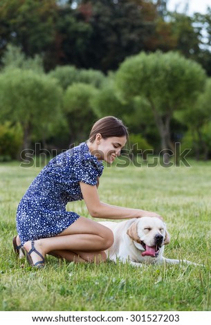 Portrait of a beautiful woman sitting on the grass with a playful young dog,and stroking her. Nature - stock photo