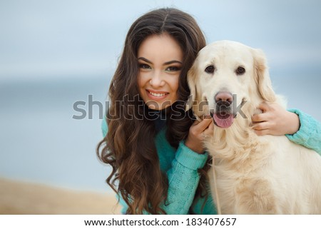 Portrait of a beautiful woman sitting on the sea shore with a playful young dog, Nature - stock photo