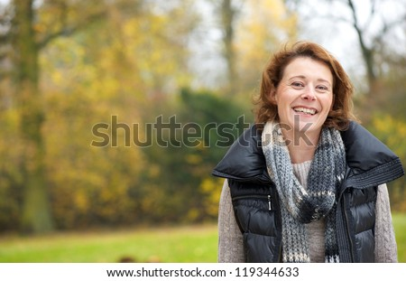Portrait of a beautiful woman smiling in the park - stock photo