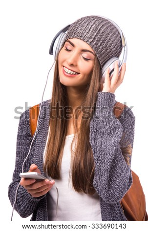 Portrait of a beautiful woman student with braces on the teeth, listening to music, isolated on a white background - stock photo
