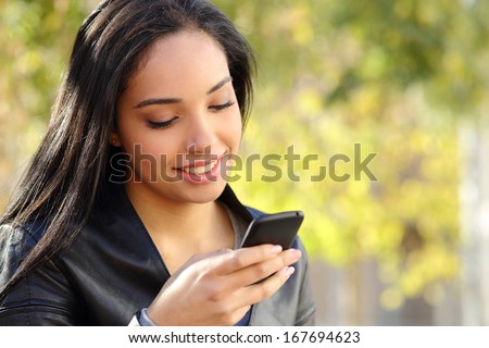 Portrait of a beautiful woman typing on the smart phone in a park with a green unfocused background          - stock photo