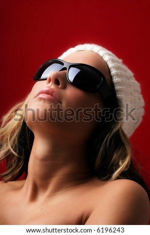 portrait of a beautiful woman with a cap and some sunglasses against red background - stock photo