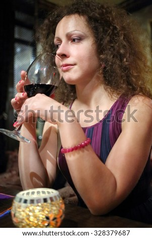 Portrait of a beautiful woman with a glass of red wine in a restaurant - stock photo