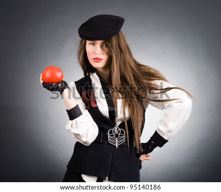 Portrait of a beautiful woman with a stylish red nut in his hand. - stock photo