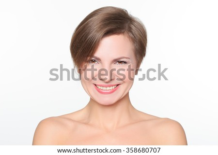 portrait of a beautiful woman with bare shoulders and short hair. wryly. - stock photo